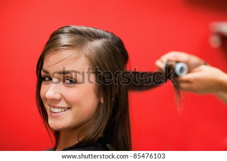 Smiling woman having her hair rolled with a curler - stock photo