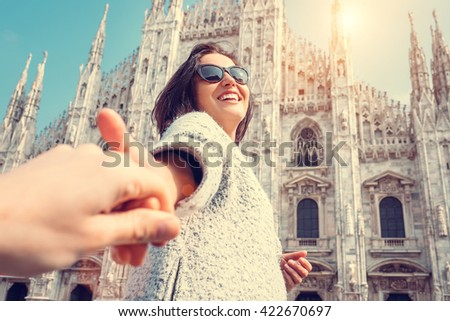 Smiling woman hold his boyfriend hand on Duomo di Milano background - stock photo