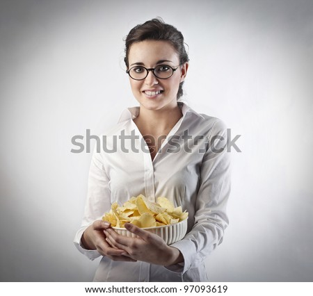 Smiling woman holding a bowl of chips - stock photo