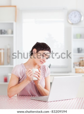 Smiling Woman holding a cup working with a laptop in a kitchen - stock photo