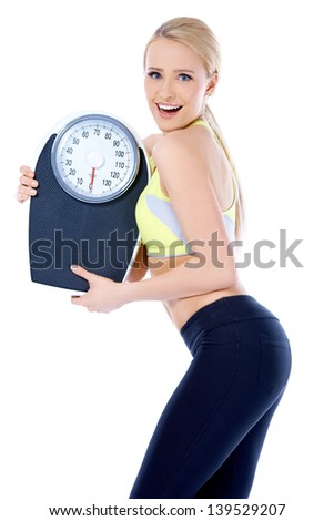 Smiling woman holding a weight scale while posing on white background - stock photo