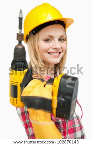 Smiling woman holding an electric screwdriver against white background - stock photo