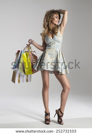 Smiling woman holding bags  - stock photo