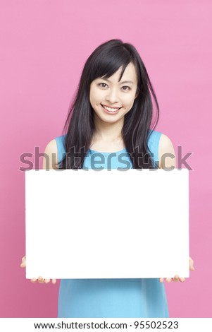 Smiling woman holding blank billboard. - stock photo