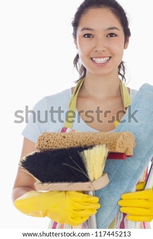 Smiling woman holding brushes and mops wearing apron and rubber gloves - stock photo
