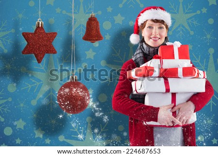 Smiling woman holding christmas presents against snowflake wallpaper pattern - stock photo