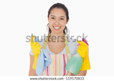 Smiling woman holding cloth and spray bottle in apron and rubber gloves - stock photo
