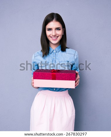 Smiling woman holding gift and looking at camera over gray background. Looking at camera  - stock photo