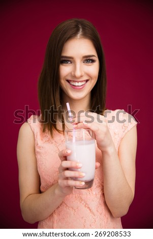 Smiling woman holding glass with yogurt over pink background. Looking at camera.  - stock photo
