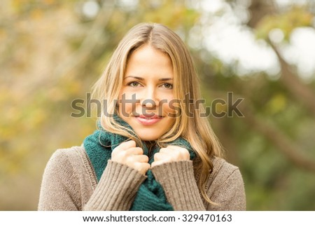 Smiling woman holding her scarf on an autumns day - stock photo