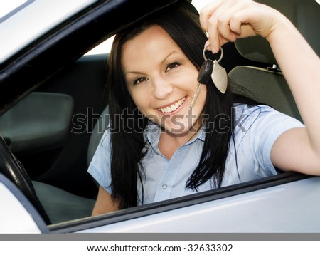 smiling woman holding key in the car - stock photo