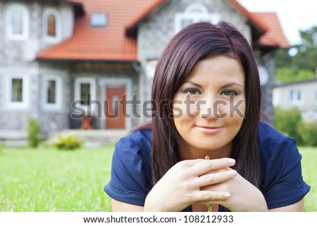 smiling woman holding keys with house background - stock photo