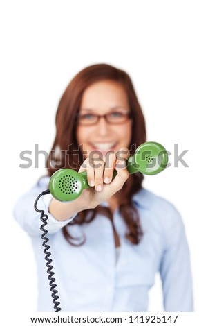 Smiling woman holding out a green telephone receiver in her hand with focus to the handset - stock photo