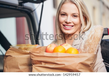 Smiling woman holding paper bags full of groceries. - stock photo