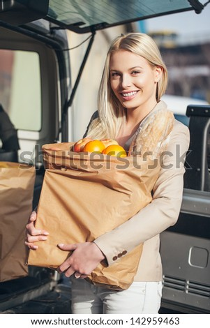 Smiling woman holding paper bags full of groceries in front of her car. - stock photo