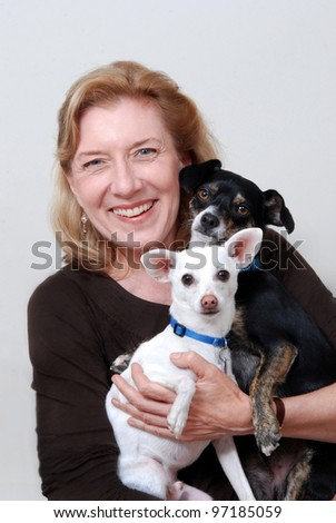 Smiling woman holding two small dogs. Isolated on white. - stock photo