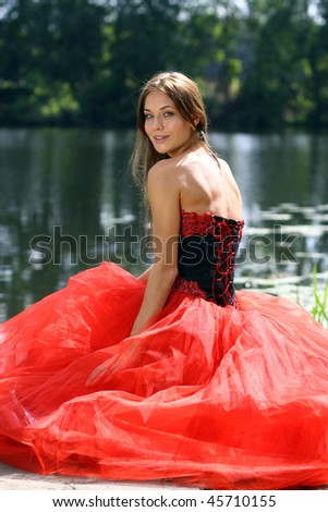 Smiling woman in a red dress sitting near river - stock photo