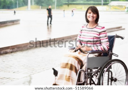 Smiling woman in a wheelchair - stock photo