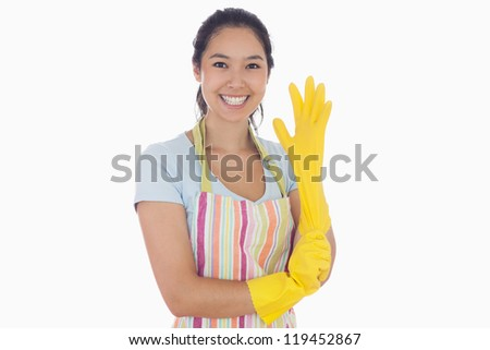 Smiling woman in apron pulling on rubber glove - stock photo
