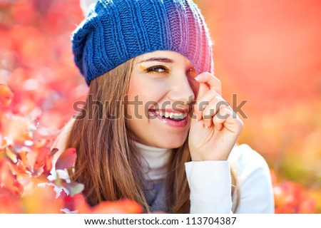 Smiling woman in autumn park - stock photo