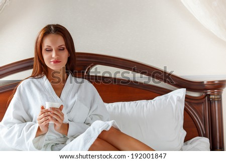 smiling woman in bedroom wearing bathrobe drinking coffee on bed - stock photo