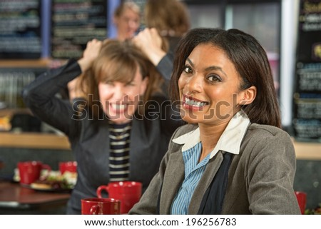 Smiling woman in coffee house with frustrated friend - stock photo