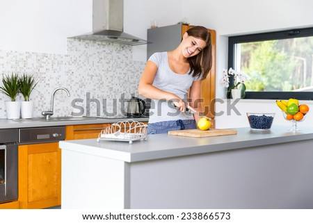 Smiling woman in kitchen slicing apple - stock photo