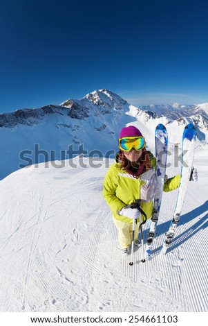 Smiling woman in mask standing and holding ski - stock photo