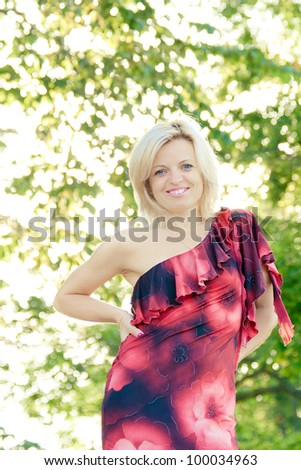 smiling woman in outdoors with green leaves in the background - stock photo