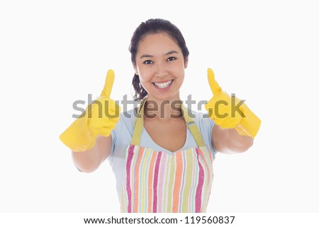 Smiling woman in rubber gloves and apron giving thumbs up - stock photo