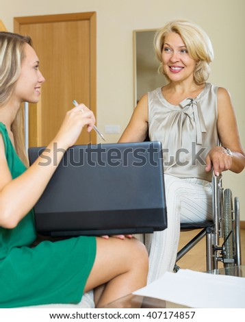 Smiling woman in wheelchair answering on questions of clerk - stock photo