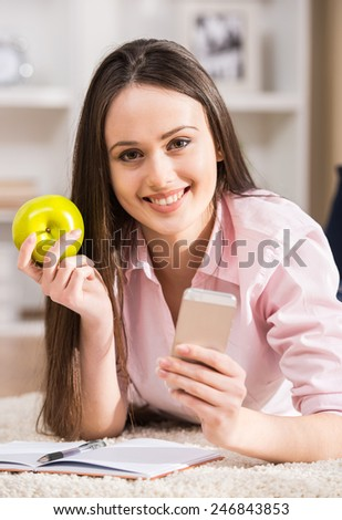 Smiling woman is holding apple and mobile phone. - stock photo