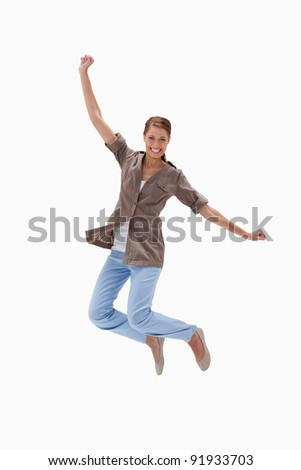 Smiling woman jumping against a white background - stock photo