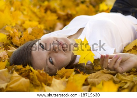 smiling woman laying on falling leaves - stock photo