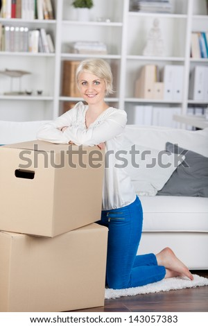 smiling woman leaning on cardbord boxes at home - stock photo
