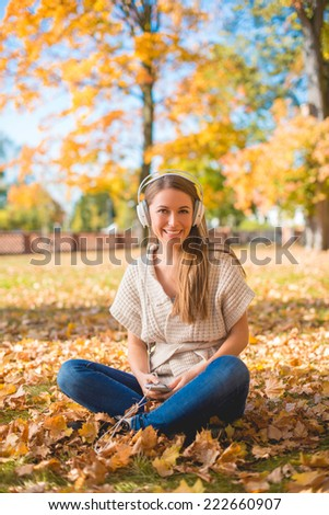 Smiling woman listening to music in a fall park sitting cross-legged amongst the fallen autumn leaves smiling at the camera - stock photo