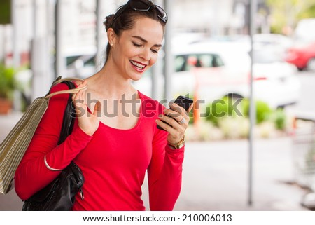 Smiling woman looking at mobile phone - stock photo