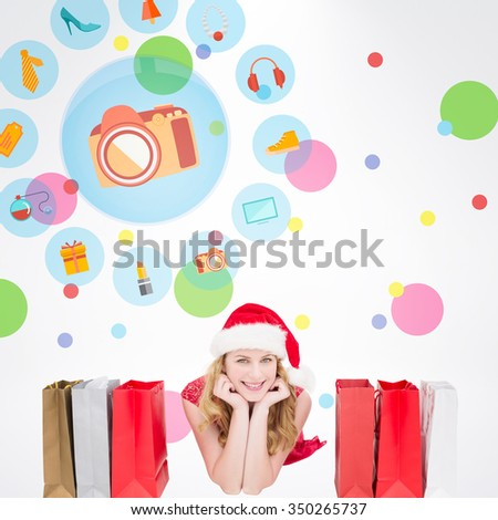 Smiling woman lying between shopping bags against dot pattern - stock photo