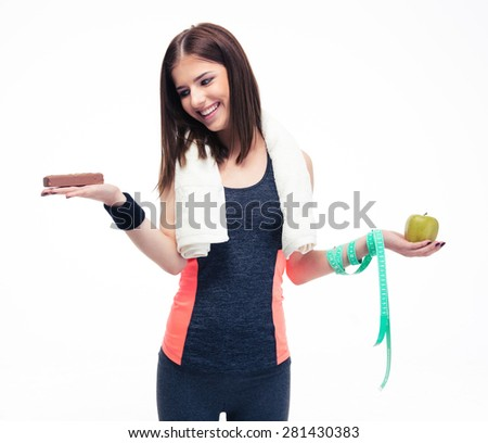 Smiling woman making choice between bananas and chocolate isolated on a white background - stock photo