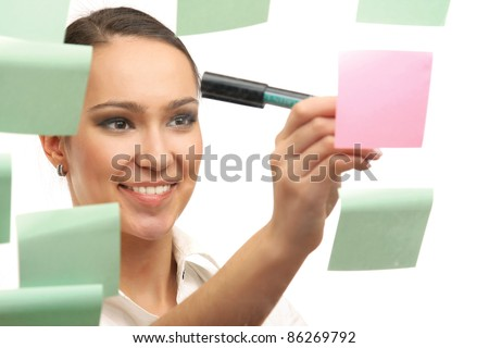 Smiling woman making notes on memo sheets isolated - stock photo
