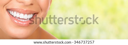 Smiling woman mouth with great teeth. Over green background