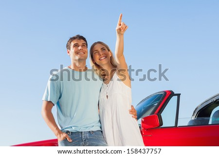 Smiling woman on blue sky background showing something to her handsome boyfriend - stock photo