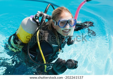Smiling woman on scuba training in swimming pool on a sunny day - stock photo