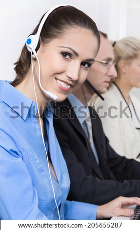 Smiling woman on the phone in a call center wearing blue blouse. - stock photo