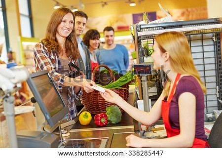 Smiling woman paying with her EC card at supermarket checkout - stock photo