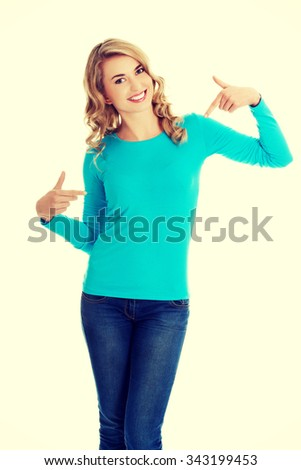 Smiling woman pointing at her shirt. - stock photo