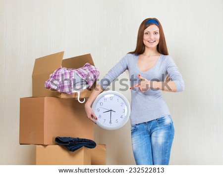 Smiling woman pointing at the clock with the moving boxes - stock photo