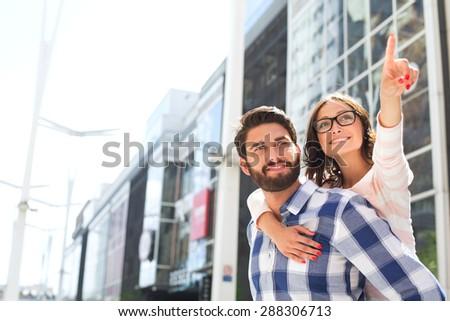 Smiling woman pointing away while enjoying piggyback ride on man in city - stock photo