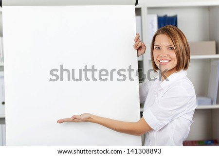 Smiling woman pointing to a a blank white flipchart with her hand while standing alongside it in the office - stock photo
