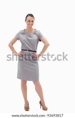 Smiling woman posing in a dress with her hands on her hips against white background - stock photo